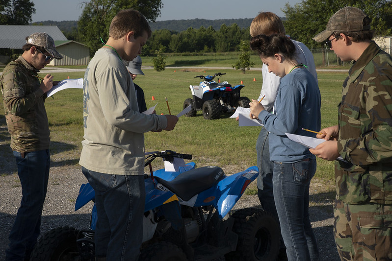 Several 4-H youth outdoors taking an ATV safety test. ATV vehicles in background.