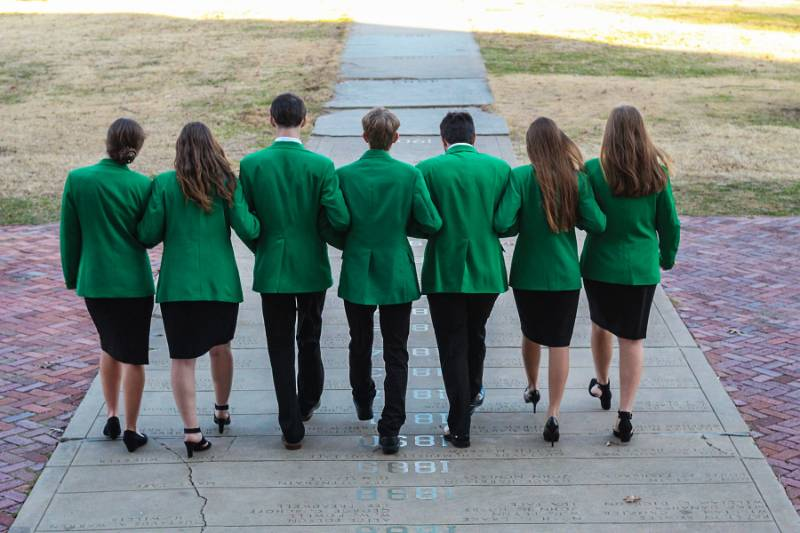 The 7 state officers in green suit jackets, walking away from the camera, linked arms.