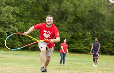 Man running with hoola-hoop in hand, other adults participating in teambuilding activties in background.