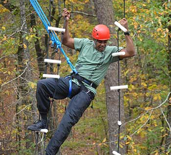 Adult male in harness and orange helmet on a high ropes course activity.
